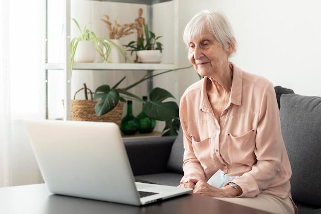 Mulher idosa usando laptop em uma casa de repouso