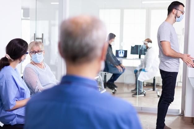 Mulher idosa usando máscara facial como precaução segura contra o coronavírus durante a pandemia global de coronavírus na sala de espera de um hospital