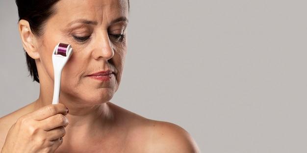Mulher idosa usando o rolo facial na pele com espaço de cópia