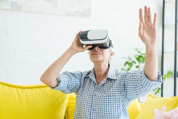Mulher idosa usando os óculos de realidade virtual