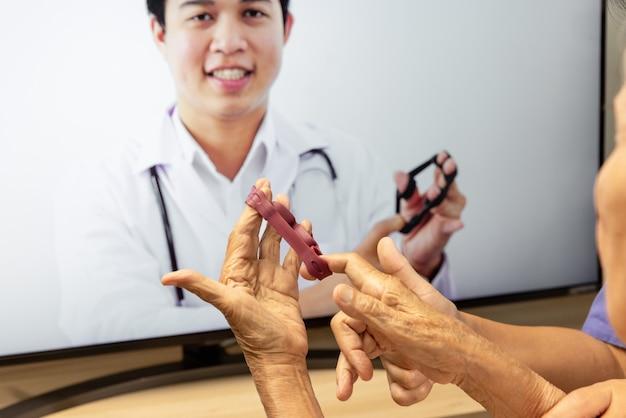 Mulher idosa usando serviço online de fisioterapia em casa.