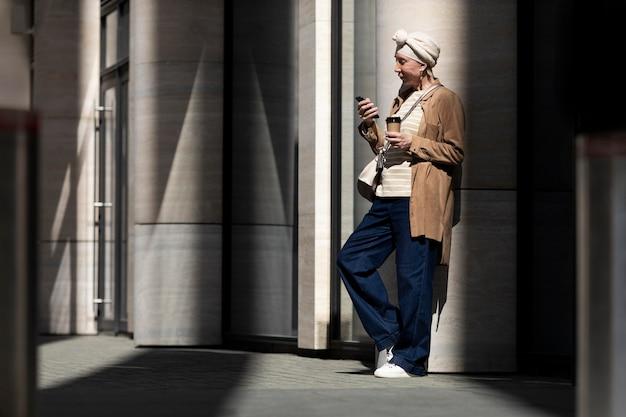 Mulher idosa usando smartphone ao ar livre na cidade