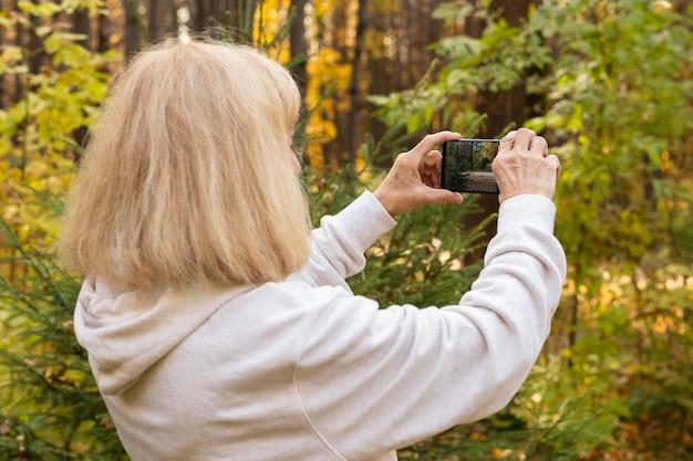 Mulher idosa usando smartphone para tirar fotos da natureza