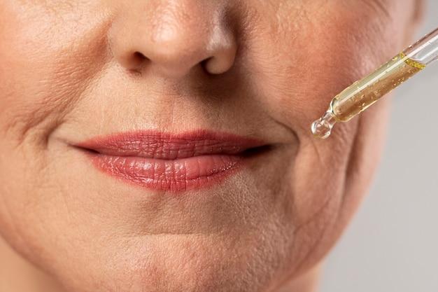 Mulher idosa usando soro para as rugas da boca