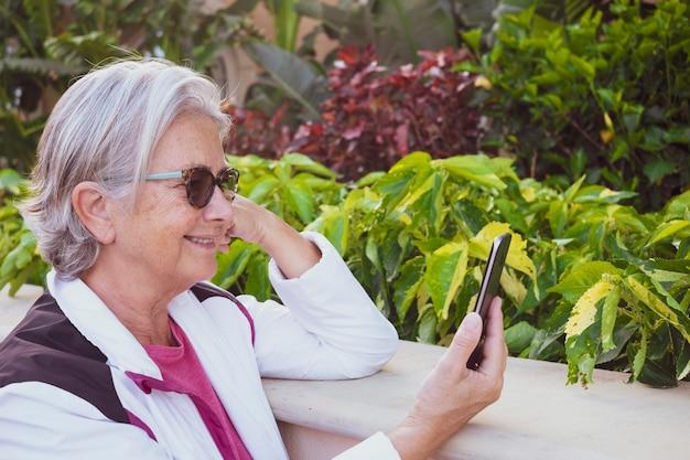 Mulher idosa usando sorrisos de celular e felicidade por um aposentado em liberdade