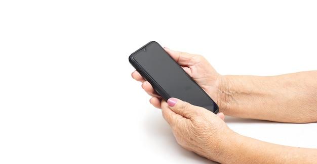 Mulher idosa usando telefone celular em ambientes fechados