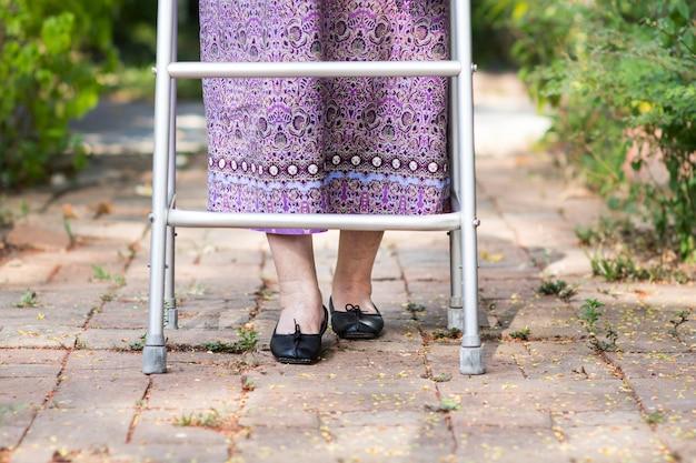 Mulher idosa usando um andador em casa.