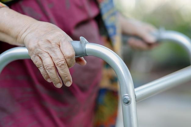 Mulher idosa usando um andador no quintal