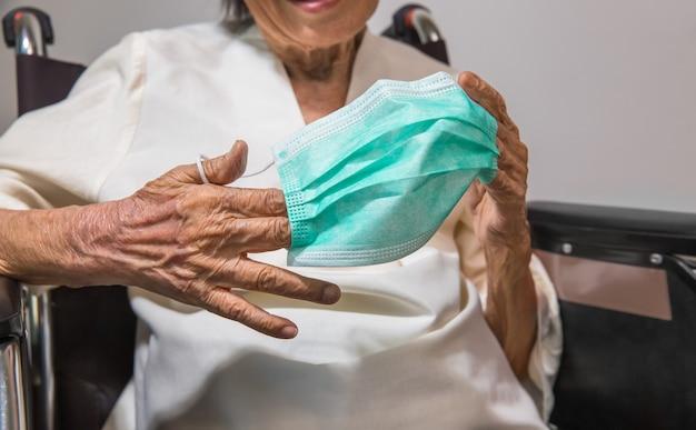 Mulher idosa usando uma máscara para proteger do coronavírus covid-19