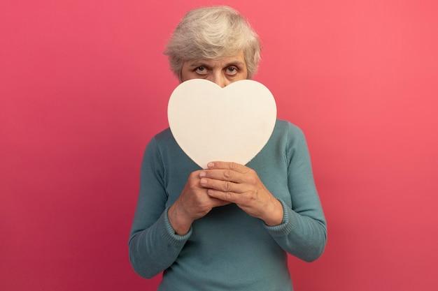 Mulher idosa vestindo um suéter de gola alta azul segurando um formato de coração olhando para frente por trás, isolado na parede rosa