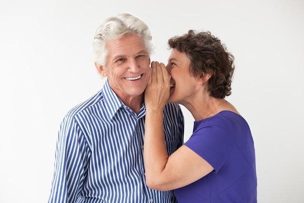 Mulher idosa whispering segredo para marido sorrir