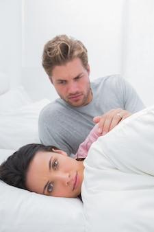 Mulher ignorando o parceiro na cama
