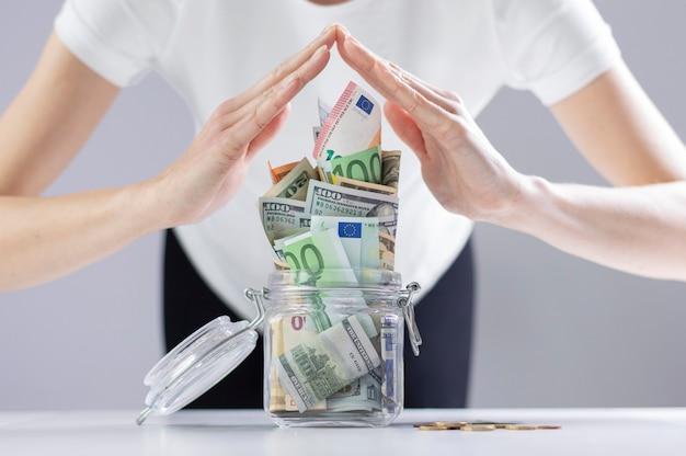 Mulher imita um teto com as mãos sobre um cofrinho cheio de notas de dinheiro