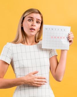 Mulher imitando cólicas estomacais da menstruação