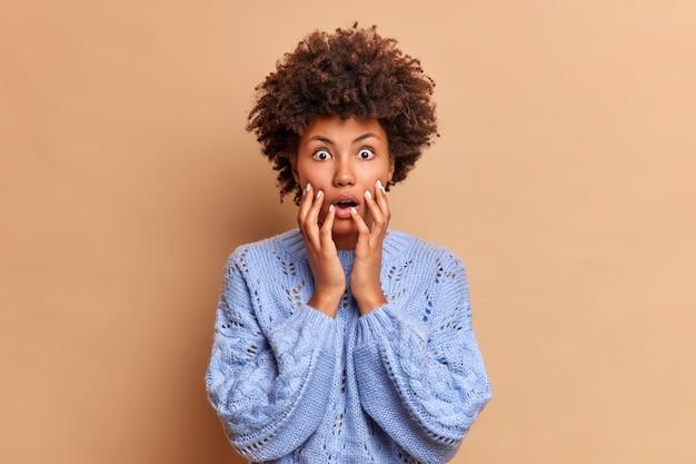 Mulher impressionada com cabelo encaracolado agarra o rosto enquanto vê algo chocante e olhos arregalados de tirar o fôlego na frente ouve notícias horríveis vestida em poses casuais de macacão contra a parede marrom