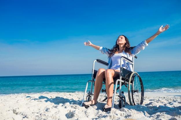 Mulher incapacitada com os braços estendidos na praia