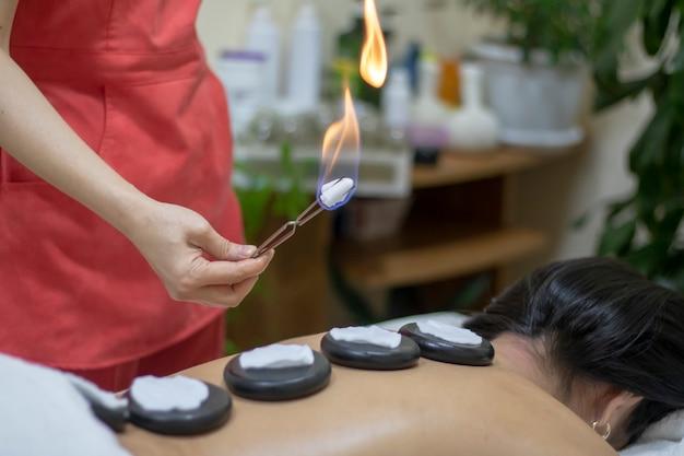 Mulher incendiando pedras de basalto zen