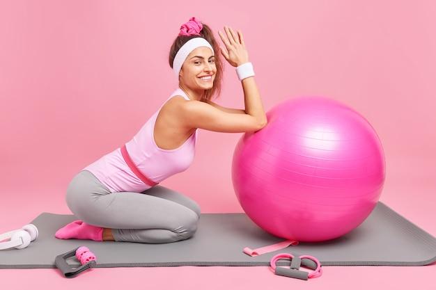Mulher inclinada para uma bola de pilates inflada faz exercícios no karemat satisfeita após o treinamento produtivo e cheia de energia