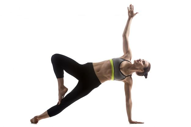 Mulher inclinada sobre um pé e um braço