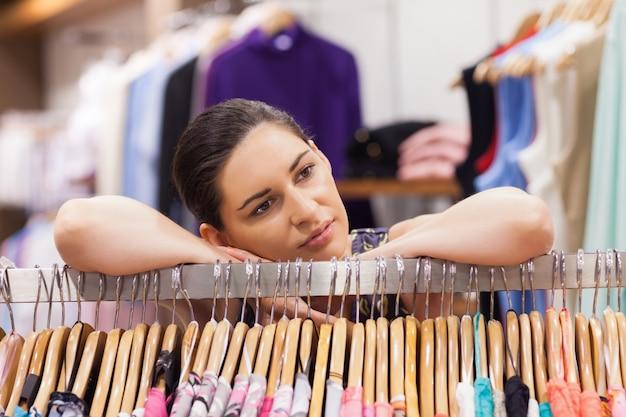 Mulher inclinada sobre uma cremalheira de roupas pensativa