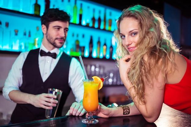Mulher, inclinar-se contador, enquanto, barman, em, fundo