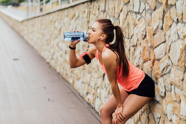 Mulher, inclinar-se, contra, parede, e, bebendo, água