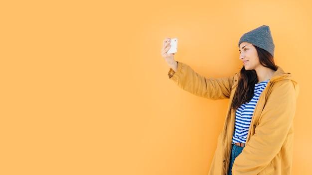 Mulher, inclinar-se, superfície, levando, selfie, ligado, telefone pilha