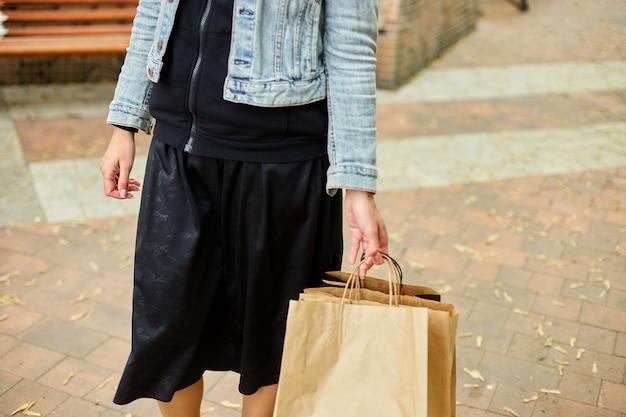 Mulher incógnita segurando vários sacos de papel com coisas compradas, caminhando ao ar livre no parque, garota depois das compras.