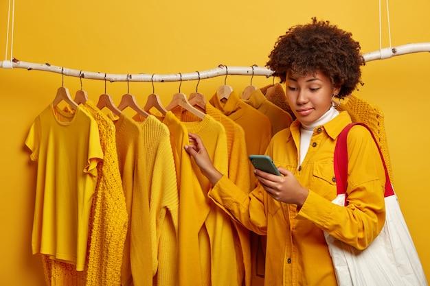 Mulher inconsciente de pele escura com penteado afro, fica perto de cabideiros amarelos, carrega uma sacola de compras no ombro, escolhe uma nova roupa