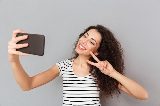 Mulher incrível com aparência caucasiana, fazendo selfie em seu smartphone, sorrindo e fazendo o gesto de vitória com dois dedos