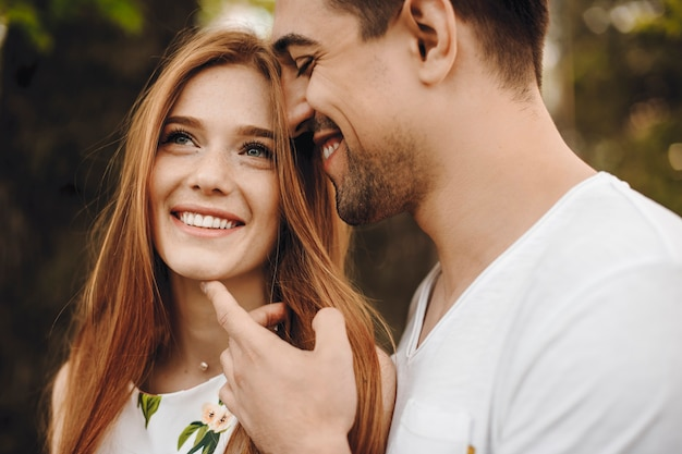 Mulher incrível com cabelo ruivo e sardas olhando para longe, sorrindo enquanto se inclina sobre o namorado, que está tocando seu rosto com a mão do lado de fora enquanto viaja.