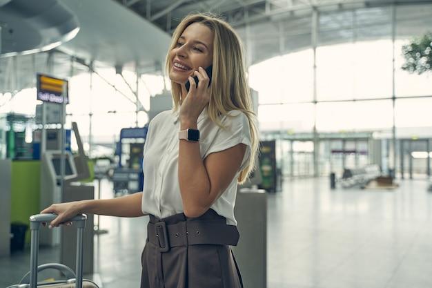 Mulher incrível de cabelos compridos no aeroporto enquanto espera seu amigo viajar de férias juntos
