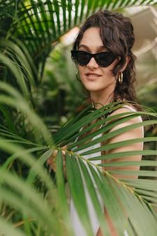 Mulher incrível e elegante com óculos escuros e lindos ganhos posando em meio a árvores exóticas