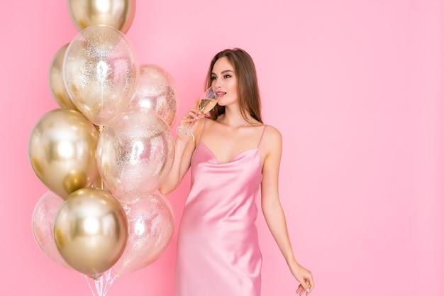 Mulher incrivelmente feliz bebe champanhe enquanto fica perto de balões de ar para comemorar