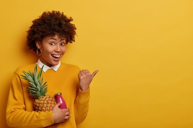 Mulher incrivelmente satisfeita tem humor feliz, segura abacaxi fresco e uma garrafa de smoothie, aponta o polegar para o lado no espaço da cópia, mantém a dieta, come frutas contendo muitas vitaminas, usa roupas amarelas