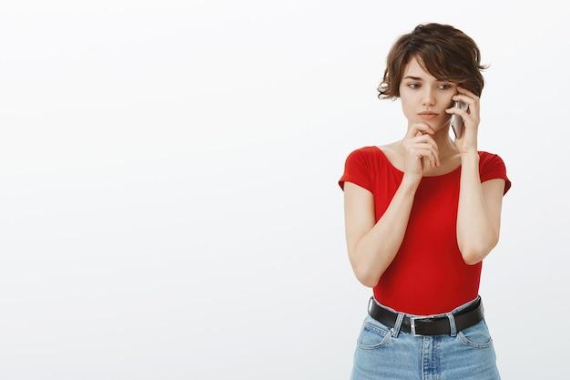 Mulher indecisa e preocupada falando ao telefone com uma expressão preocupada