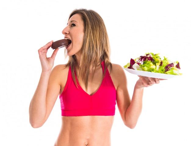 Mulher indecisa entre um donut e uma salada