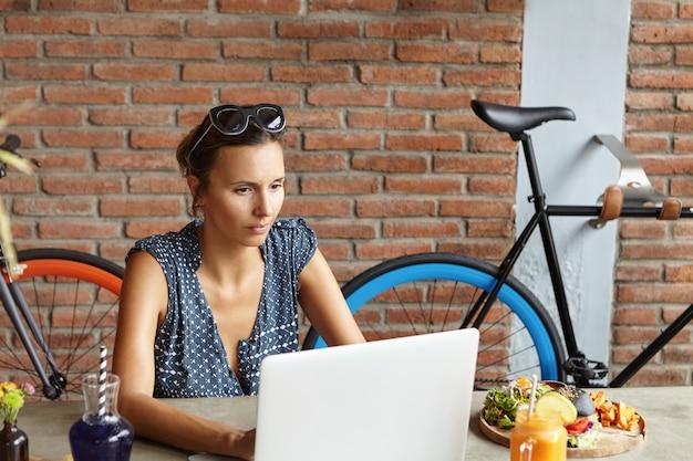 Mulher independente séria e confiante vestida casualmente digitando no computador laptop moderno enquanto estiver usando o dispositivo eletrônico para trabalho remoto