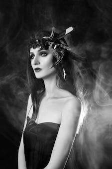 Mulher indiana com penas no cabelo, retrato da beleza da menina índia americana em fundo escuro na fumaça. rosto lindo com pele limpa, maquiagem contrastante