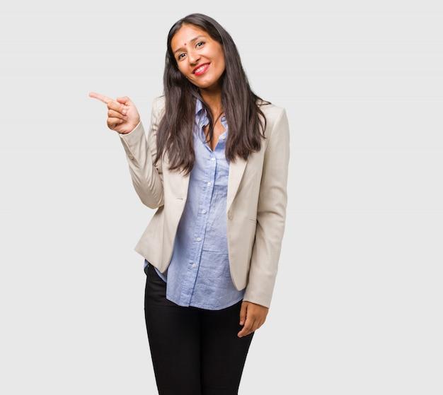 Mulher indiana de negócios jovem apontando para o lado, sorrindo surpreendeu apresentando algo, natural e casual