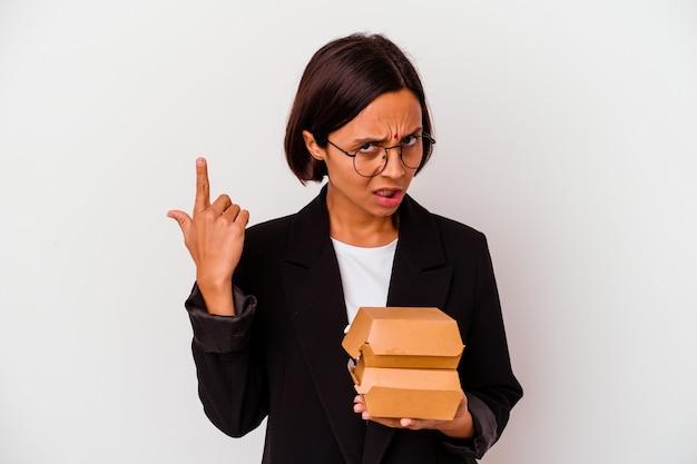 Mulher indiana de negócios jovem comendo hambúrgueres isolados, mostrando um gesto de decepção com o dedo indicador.