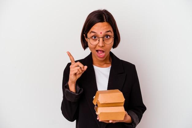 Mulher indiana de negócios jovem comendo hambúrgueres isolados, tendo uma ideia, o conceito de inspiração.