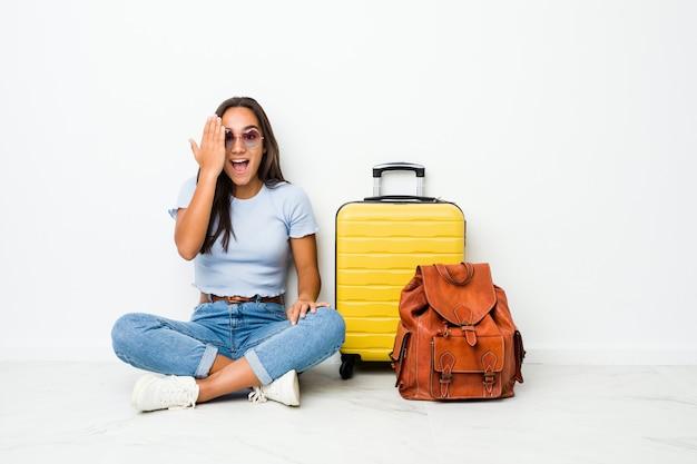 Mulher indiana de raça mista jovem pronta para ir viajar se divertindo cobrindo metade do rosto com a palma da mão.