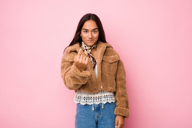 Mulher indiana de raça mista jovem vestindo um casaco de pele de carneiro curto, apontando com o dedo para você como se estivesse convidando para se aproximar.