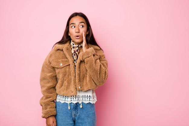 Mulher indiana de raça mista jovem vestindo um quatis de pele de carneiro curto dizendo uma notícia secreta sobre frenagem quente e olhando de lado