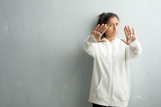 Mulher indiana desportiva nova contra uma parede do gym séria e determinada