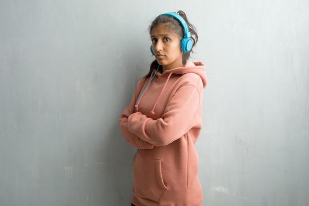 Mulher indiana desportiva nova contra uma parede que cruza seus braços, sérios e imponentes