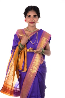 Mulher indiana em adoração, retrato de uma bela jovem com pooja thali isolado na parede branca