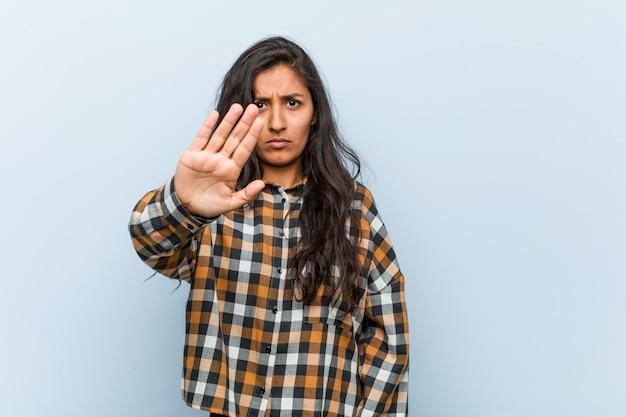 Mulher indiana fresca nova que está com a mão outstretched que mostra o sinal da parada, impedindo-o.