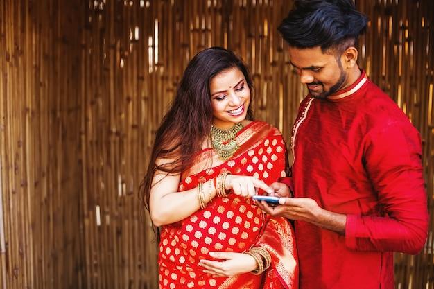 Mulher indiana grávida feliz com o marido usando o telefone